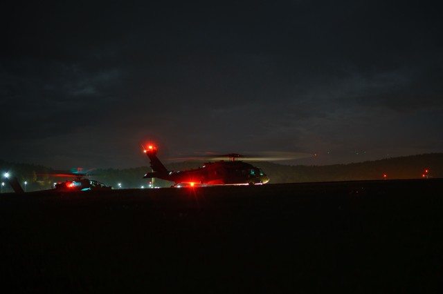 An AH-64 Apache helicopter flight crew, left, with 1st Attack Reconnaissance Battalion, prepares to escort a UH-60 Black Hawk helicopter crew, right, with 3rd Assault Helicopter Battalion, both with the 227th Aviation Regiment, 1st Air Cavalry Brigade, 1st Cavalry Division, during a night training mission at Hohenfels Training Area, Germany, April 23, 2018.