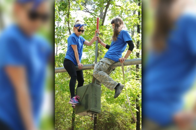 Erin Allsop and Talitha Fagen, military spouses, work together as they try to move an ammunition container across an obstacle at the Leaders Reaction Course during Aviation Spouses Day April 19.