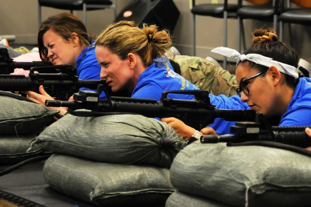 Spouses practice marksmanship during a simulated weapons qualification event.