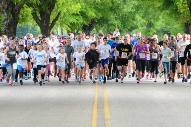 Runners, clad with gold stars representing fallen service members, make their way through the course during the Survivors and Fallen Heroes 5k run April 21 at the Fort Rucker Physical Fitness Center.
