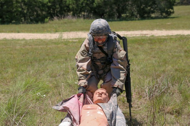Sgt. Anthony Brown-Davis pulls a human-sized dummy during a combat lane event at the Best Warrior Competition at Camp Bullis.