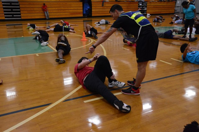 Staff Sgt. Jacob Sejat, a drill sergeant with Bravo Company, 1st Battalion, 46th Infantry Regiment, at Fort Benning, Georgia, instructs a student on the proper way to conduct a stretch during the student's physical fitness education class April 26, 2018, at Midland Middle School in Columbus, Georgia. The event was a part of Fort Benning's Partners in Education program, which partners military units with schools in the local area. (Photo by Megan Garcia, Maneuver Center of Excellence, Fort Benning Public Affairs)