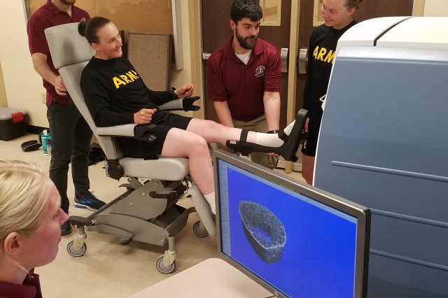 During a data collection at Fort Jackson, South Carolina, the principal investigators of the ARIEM Reduction in Musculoskeletal Injury, or ARMI, study, Dr. Julie Hughes, bottom left, and Dr. Stephen Foulis, middle, both research physiologists from the U.S. Army Research Institute of Environmental Medicine, or USARIEM, use a high-resolution scanner to image a female recruit's bone and muscle microstructure in an effort to understand how recruits' bones and muscles change during Basic Combat Training and what factors can affect injury risk.