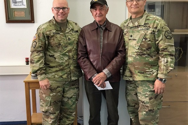 Roland Lutz visits with Chaplain (Lt. Col.) Suk Kim (right) and Sgt. 1st Class Kristopher Norville in the Katterbach Chapel, which used to be his workplace many years ago April 26,2018.