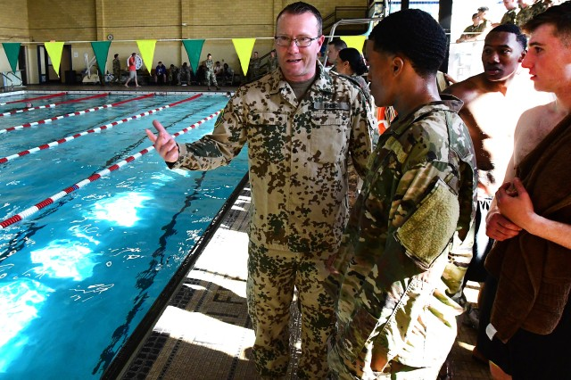 Lt. Col. Daniel Krebs, a German Army officer and professor at the University of Louisville, encourages some Soldiers during the swim event. German regulations require that a German officer officiate the competition to ensure standards are met.