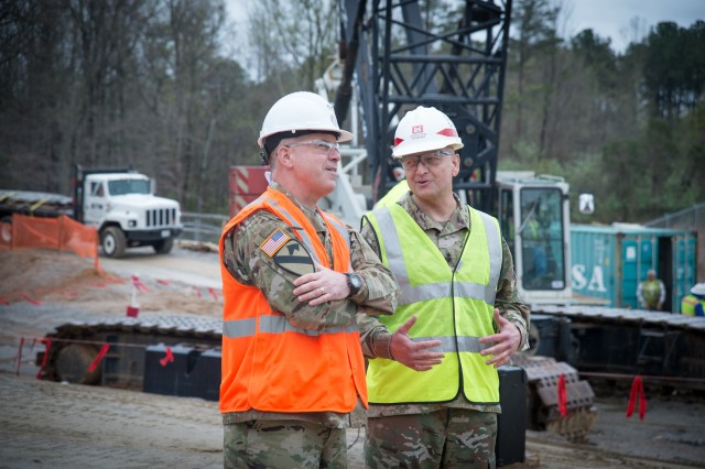 Maj. Gen. Christopher S. Ballard (left), commanding general, U.S. Army Intelligence and Security Command and Maj. Gen. Anthony C. Funkhouser, deputy commanding general for military and international operations, U.S. Army Corps of Engineers, chat while the last structural beam is lifted into place of the new addition to the Nolan Building during the INSCOM Topping Out Ceremony, Fort Belvoir, Virginia, Apr. 16. A Topping Out is a ceremony held when the last steel beam is placed at the top of a building. This tradition comes from European craftsmen when they migrated to America. The Topping-Out beam is signed by those who were significant throughout the building's construction.