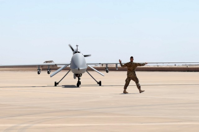 Undisclosed Location - U.S. Army Spc. Benjamin Crandall, a Soldier assigned to Company B, 229th Aviation Regiment, 449th Combat Aviation Brigade ground guides a MQ-1C Gray Eagle Unmanned Aircraft System to a launchpad after an aerial reconnaissance flight March 31, 2018. Company B is currently deployed in the Southeast Asia region utilizing the MQ-1C Gray Eagle Unmanned Aircraft Systems that conducts reconnaissance and attack operations enabling U.S., Coalition and partner nations to defeat and destroy ISIS in support of Operation Inherent Resolve. (U.S. Army photo by Spc. Devin Fleming, 449th Combat Aviation Brigade)