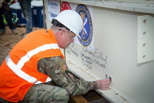 Maj. Gen. Christopher S. Ballard, commanding general, U.S. Army Intelligence and Security Command, affixes coins to the ceremonial steel beam at the Nolan Building expansion project Topping Out Ceremony, Fort Belvoir, Virginia, Apr. 16. A Topping Out is a ceremony held when the last steel beam is placed at the top of a building. This tradition comes from European craftsmen when they migrated to America. The Topping-Out Beam is signed by those who were significant throughout the building's construction.