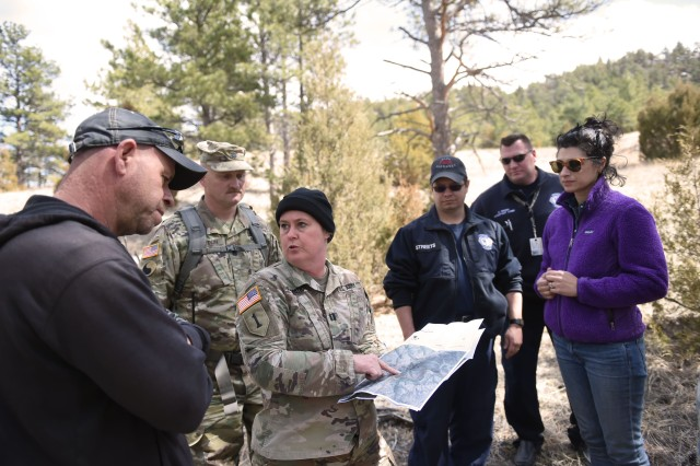 Capt. Sabrina Kirkpatrick, environmental officer, discusses a potential fire break in an area of Sawmill Canyon on Camp Guernsey's North Training Area with Matt Martin, a heavy equipment operator with the camp's Public Works Department, April 5, 2018, during a site visit. Along for the hike are Deputy Commander lt. col. William Patton, Camp Guernsey Fire Department Station Captain Mark Streets, Assistant Fire Chief Chad Brush and Natural Resources Manager Amanda Thimmayya.