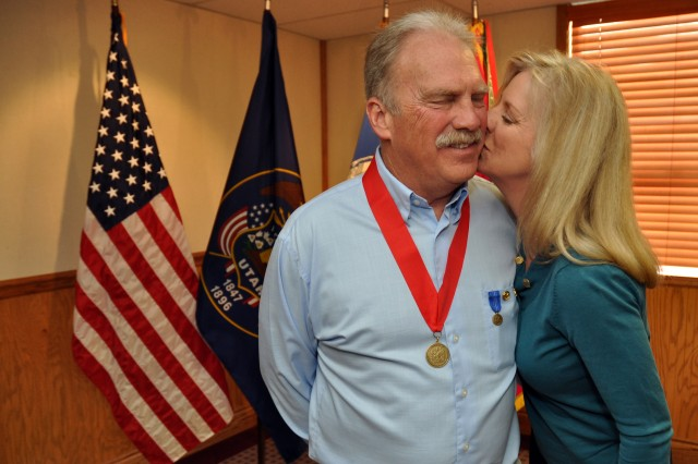 Frances Siniscalchi kisses her husband, Keith Siniscalchi, civilian deputy to the commander, Tooele Army Depot, after she pinned the Department of Defense retirement pin onto his pocket during his retirement ceremony April 30, after more than 35 years of service. The Siniscalchi's met at the Depot more than 25 years ago.