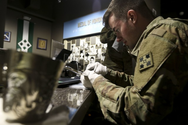 Spc. Zach Ambrose of 1st Battalion, 38th Infantry Regiment, 1st Stryker Brigade Combat Team, 4th Infantry Division polishes the over two foot long silver ladle that accompanies the Liscum Bowl April 24, 2018, prior to the unveiling of the ornate artifact at the Fort Carson Museum at Fort Carson, Colorado. The Liscum Bowl is a silver punch bowl, made from more than 90 pounds of silver bullion that was seized by the 9th Infantry Regiment during the Boxer Rebellion in 1900 and was presented to the regiment as a token of appreciation for its action during the conflict. The bowl had been on display in the 2nd Infantry Division museum at Camp Casey, South Korea, but it was recently returned to the 4th Battalion, 9th Infantry Regiment, the only active duty element of the 9th Infantry Regiment still in existence, and will be displayed at the Fort Carson Museum. (U.S. Army photo by Staff Sgt. Leah R. Kilpatrick)