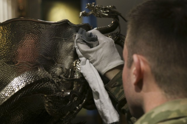 Spc. Zach Ambrose of 1st Battalion, 38th Infantry Regiment, 1st Stryker Brigade Combat Team, 4th Infantry Division polishes the Liscum Bowl April 24, 2018 prior to the unveiling of the ornate artifact at the Fort Carson Museum at Fort Carson, Colorado. The Liscum Bowl is a silver punch bowl, made from more than 90 pounds of silver bullion that was seized by the 9th Infantry Regiment during the Boxer Rebellion in 1900 and was presented to the regiment as a token of appreciation for its action during the conflict. The bowl had been on display in the 2nd Infantry Division museum at Camp Casey, South Korea, but it was recently returned to the 4th Battalion, 9th Infantry Regiment, the only active duty element of the 9th Infantry Regiment still in existence, and will be displayed at the Fort Carson Museum. (U.S. Army photo by Staff Sgt. Leah R. Kilpatrick)
