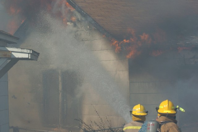 Red River Army Depot firefighters provide assistance in a house fire in Hooks, Texas. The depot provides mutual aid support to surrounding communities.