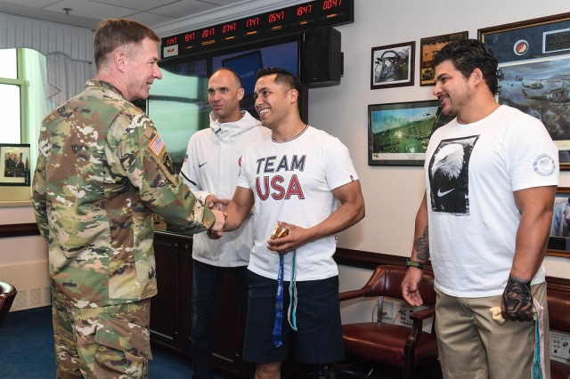 Gen. James McConville, Vice Chief of Staff of the Army, shakes hands with former Army Staff Sgt. Rico Roman. Roman is a member of the 2018 gold-medal winning USA sled hockey team. Former Army Spc. Andy Soule, far left, and former Marine Corps Gunnery Sgt. Ralph DeQuebec, far right, were also among those who met with the general, April 24, 2018 in the Pentagon.