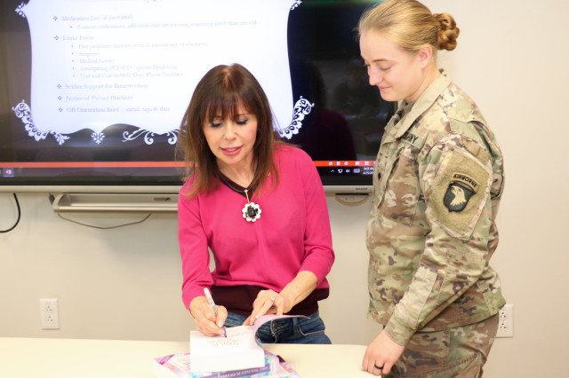 Best-selling author of the What to Expect series, Heidi Murkoff, signs a copy of her book What to Expect When Expecting for Spc. Savannah Tuepker, a participant at an orientation session for active-duty Soldiers at the Women's Health Clinic at Blanchfield Army Community Hospital, April 25. Murkoff also visited women at the hospital's Mother Baby Unit who had recently delivered. The author was on Fort Campbell for the USO Special Delivery Baby Shower and made time to visit patients and staff at Blanchfield before the event. U.S. Army photo by Maria Yager.