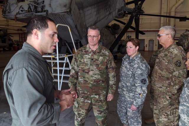Staff Sgt. Billy Egipciaco, flight line division chief from the 772nd Marine Heavy Helicopter Squadron is discussing loading and unloading procedures to Lt. Col. Charles Foreman, Maj. Julie Birmingham and Maj. Desmond Nelson of the 7221st Medical Support Unit during their training at Joint Base McGuire Dix Lakehurst, New Jersey.