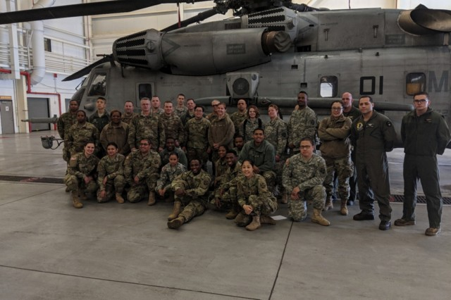 Soldiers from the 7221st Medical Support Unit and US Marines from the 772nd Marine Heavy Helicopter Squadron are posing for a group picture in front of a CH53E Super Stallion Helicopter after completing their joint training.