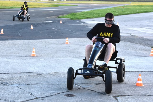 WIESBADEN, Germany -- Team members navigate a driving course on pedal cars while wearing drunk goggles at a challenge during the SHARP Amazing Race April 19, 2018 at Clay Kaserne.