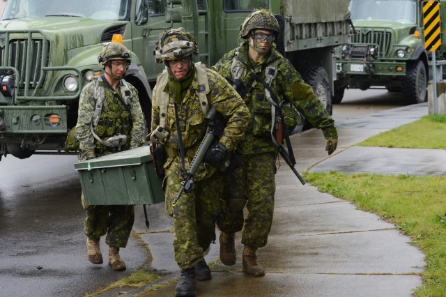 Soldiers assigned to the 39th Canadian Brigade Group move equipment from supply vehicles into the 'Leschi Town' training village at Joint Base Lewis-McChord, Washington, April 28, 2018. Soldiers from the Oregon National Guard and Canada took part in four-days of training as part of Exercise Cougar Rage, April 26-29.