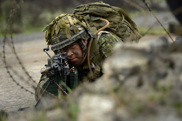 Canadian Army Reservists Private James Choi, assigned to the 39th Brigade Group, Vancouver, British Columbia, holds a defensive position outside of the training village of 'Leschi Town', as members of his platoon wait to advance to the next position during Exercise Cougar Rage, April 28, 2018, at Joint Base Lewis-McChord, Washington. Soldiers from the Oregon Army National Guard and Canada integrated four days of training during the exercise.