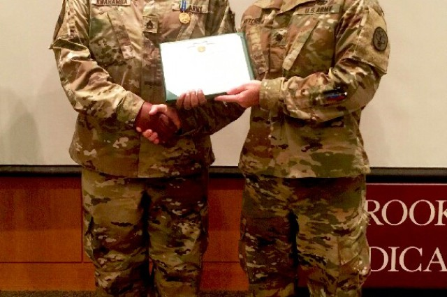 Lt. Col. James Mitchell, Joint Base San Antonio's Warrior Transition Battalion Commander presents Staff Sgt. Claymore Kwaramba with the Compassionate Leader Award for 3rd quarter FY2017