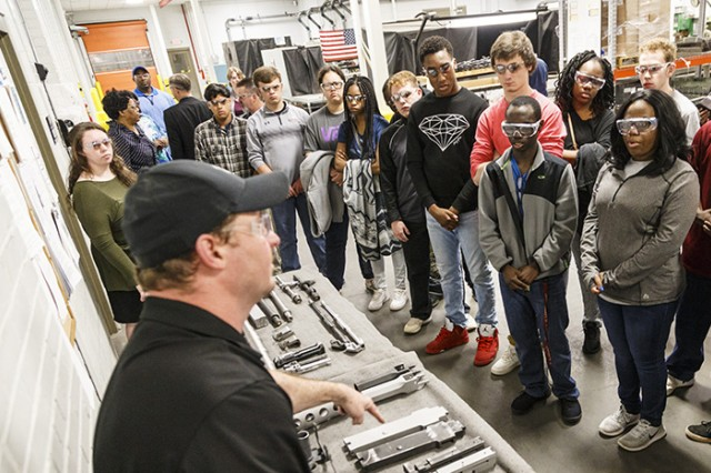 Jason Morgan discusses the cleaning and metal coating processes with students from the Alabama School for the Deaf.