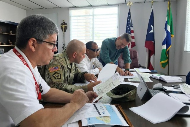 "Jose Cedeno-Maldonado (left), U.S. Army Maj. Alexander Walker (center), both community liaisons with Task Force Power Restoration, and Martin Wah, Puerto Rico Electric Power Authority Barranquitas District Engineer, meet with Mayor of Orocovis Jesús ""Gardi"" Colón Berlingeri to dialogue about electrical restoration work underway in Orocovis. Community liaisons keep municipalities informed about power restoration efforts in a timely manner by frequently providing them data, including schedules and descriptions of where crews will be working and what they will be doing. They meet with mayors and their staffs to listen to their questions, concerns, and recommendations then bring back that information to task force leadership for further action."