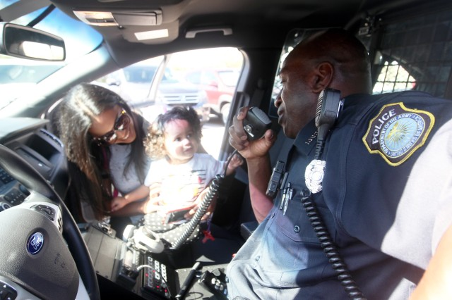 Patrol officer Kevin D. Jones demonstrates the loud speakers to his police vehicle to Victoria Quinones, 1, daughter of 1st Lt. Jose Quinones, 100th Brigade Support Battalion; and her mother Paola. Children learned about those who protect people on post during Imagine a Safer Future, April 26, 2018, at the Fort Sill Youth Center.