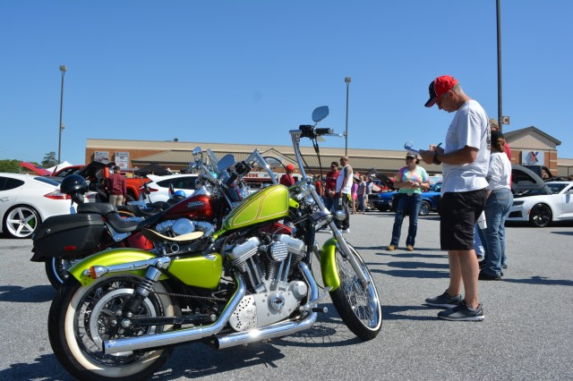 FORT BENNING, Ga. (May 3, 2018) - Bobby McCloskey, right, judges import motorcycles. Volunteers, both individual and belonging to automobile clubs, brought 95 classic and otherwise unique vehicles April 28 to the main Post Exchange at Fort Benning, Georgia, to highlight the Army's efforts in sexual assault prevention, survivor support, de-stigmatization of reporting and community cooperation. Members of the Sexual Harassment and Assault Response and Prevention (SHARP) and Better Opportunities for Single Soldiers (BOSS) programs and others organized the Teal Wheels automobile show as part of April as Sexual Assault Awareness and Prevention Month. (U.S. Army photo by Bryan Gatchell, Maneuver Center of Excellence, Fort Benning Public Affairs / RELEASED)