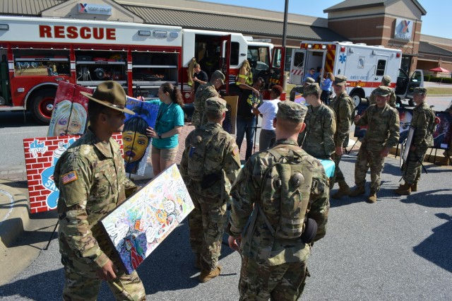 FORT BENNING, Ga. (May 3, 2018) - Soldiers help place SHARP-themed works of art on easels. Volunteers, both individual and belonging to automobile clubs, brought 95 classic and otherwise unique vehicles April 28 to the main Post Exchange at Fort Benning, Georgia, to highlight the Army's efforts in sexual assault prevention, survivor support, de-stigmatization of reporting and community cooperation. Members of the Sexual Harassment and Assault Response and Prevention (SHARP) and Better Opportunities for Single Soldiers (BOSS) programs and others organized the Teal Wheels automobile show as part of April as Sexual Assault Awareness and Prevention Month. (U.S. Army photo by Bryan Gatchell, Maneuver Center of Excellence, Fort Benning Public Affairs / RELEASED)