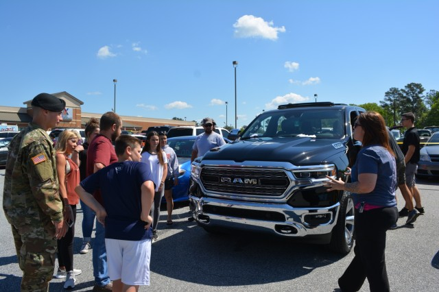 FORT BENNING, Ga. (May 3, 2018) - Angela Robinson tells attendees at the Teal Wheels car and motorcycle show about her 2019 Dodge Ram. Volunteers, both individual and belonging to automobile clubs, brought 95 classic and otherwise unique vehicles April 28 to the main Post Exchange at Fort Benning, Georgia, to highlight the Army's efforts in sexual assault prevention, survivor support, de-stigmatization of reporting and community cooperation. Members of the Sexual Harassment and Assault Response and Prevention (SHARP) and Better Opportunities for Single Soldiers (BOSS) programs and others organized the Teal Wheels automobile show as part of April as Sexual Assault Awareness and Prevention Month. (U.S. Army photo by Bryan Gatchell, Maneuver Center of Excellence, Fort Benning Public Affairs / RELEASED)