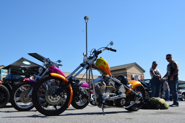 FORT BENNING, Ga. (May 3, 2018) - Laura Hall, second from left, and husband Dustin, right, stand next to their respective 2007 Harley-Davidson Sportster and 2009 full custom motorcycles. Volunteers, both individual and belonging to automobile clubs, brought 95 classic and otherwise unique vehicles April 28 to the main Post Exchange at Fort Benning, Georgia, to highlight the Army's efforts in sexual assault prevention, survivor support, de-stigmatization of reporting and community cooperation. Members of the Sexual Harassment and Assault Response and Prevention (SHARP) and Better Opportunities for Single Soldiers (BOSS) programs and others organized the Teal Wheels automobile show as part of April as Sexual Assault Awareness and Prevention Month. (U.S. Army photo by Bryan Gatchell, Maneuver Center of Excellence, Fort Benning Public Affairs / RELEASED)