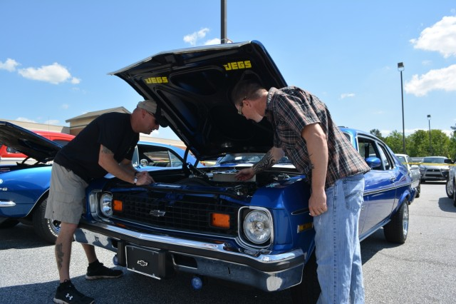 FORT BENNING, Ga. (May 3, 2018) - Staff Sgt. Robert Moorman, right, C Company, 1st Battalion, 50th Infantry Regiment, shows off the engine of his 1974 Chevy Nova to Sgt. 1st Class Matt Powell, left, Army Marksmanship Unit, during a car show at Fort Benning. Volunteers, both individual and belonging to automobile clubs, brought 95 classic and otherwise unique vehicles April 28 to the main Post Exchange at Fort Benning, Georgia, to highlight the Army's efforts in sexual assault prevention, survivor support, de-stigmatization of reporting and community cooperation. Members of the Sexual Harassment and Assault Response and Prevention (SHARP) and Better Opportunities for Single Soldiers (BOSS) programs and others organized the Teal Wheels automobile show as part of April as Sexual Assault Awareness and Prevention Month. (U.S. Army photo by Bryan Gatchell, Maneuver Center of Excellence, Fort Benning Public Affairs / RELEASED)