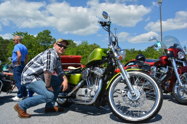 FORT BENNING, Ga. (May 3, 2018) - Staff Sgt. Randall Kisner, A Company, 1st Battalion, 50th Infantry Regiment, crouches next to his 2007 Harley-Davidson Sportster. Volunteers, both individual and belonging to automobile clubs, brought 95 classic and otherwise unique vehicles April 28 to the main Post Exchange at Fort Benning, Georgia, to highlight the Army's efforts in sexual assault prevention, survivor support, de-stigmatization of reporting and community cooperation. Members of the Sexual Harassment and Assault Response and Prevention (SHARP) and Better Opportunities for Single Soldiers (BOSS) programs and others organized the Teal Wheels automobile show as part of April as Sexual Assault Awareness and Prevention Month. (U.S. Army photo by Bryan Gatchell, Maneuver Center of Excellence, Fort Benning Public Affairs / RELEASED)