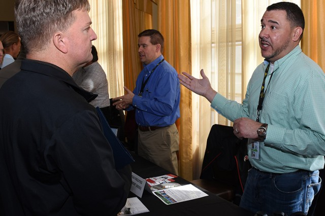 180412-A-BB276-004 Small Business Vendor Fair at Dugway Proving Ground, Utah for the public April 12, 2018. James Waltz, quality control manager for Chenega Facilities Management, discusses his company's work at Dugway with a visitor. The event was sponsored by the Mission and Installation Contracting Command (MICC) office at Dugway, and the regional MICC office that oversees Fort Carson, Colorado; Fort Sill, Oklahoma; and Dugway. Photo by Al Vogel, Dugway Proving Ground Public Affairs