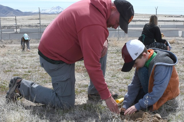180418-A-BB276-005 Robbie Knight, wildlife biologist at Dugway Proving Ground, Utah, helps a youngster plant a native seedling during the post's April 18, 2018 observance of Earth Day. Photo by Al Vogel, Dugway Proving Ground Public Affairs