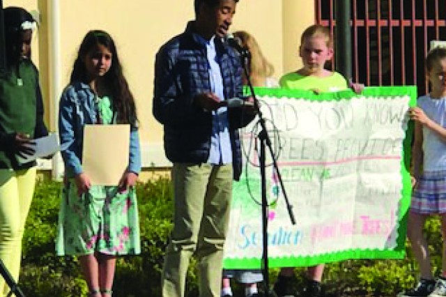 Luca Powell, at the microphone, gives a speech during the Earth Day event at Vicenza Elementary/Middle School. Powell, a middle school student, was chosen, along with two other students, to share his speech about Earth Day and improving the environment.