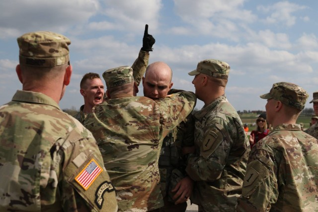 FORT LEONARD WOOD, Missouri -- Master Sgt. Jason Poulin (middle) of the 1st Engineer Battalion, 1st Armored Brigade Combat Team, 1st Infantry Division, embraces Sgt. Gary Coggins, a native of Mountain Home, Arkansas, a combat engineer also with 1st Eng. Bn., 1st ABCT, 1st Inf. Div., as he cross the finish line during the 2018 Lieutenant General Robert B. Flowers Best Sapper Competition at Fort Leonard Wood, Missouri, April 18. (Sgt. Elizabeth Jones, 19th Public Affairs Detachment)