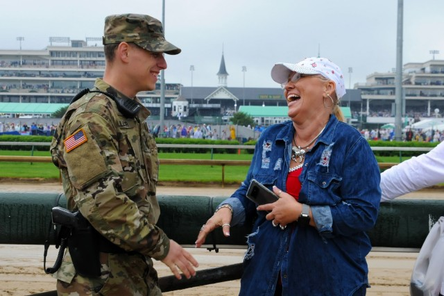 Kentucky Army National Guardsman, Spc. Roy Miller, 617th MP Co, converses with an attendee of the 144th Kentucky Derby at Churchill Downs May 5, 2018.