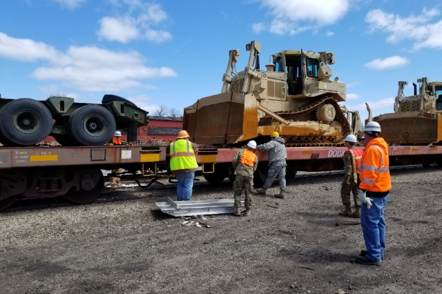Members of the Missouri Army National Guard's 220th Engineer Company work with BNSF Railway representatives to perform rail upload operations.
