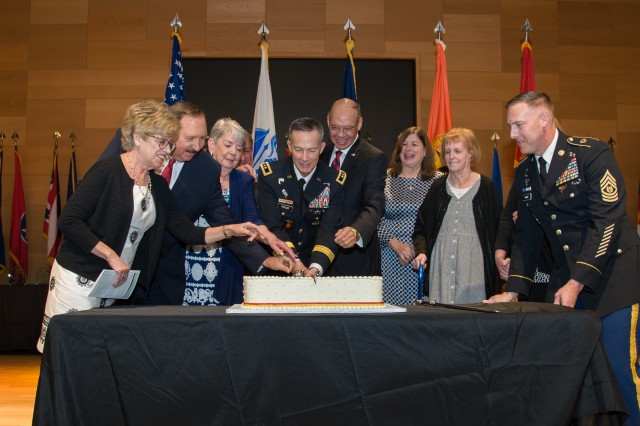 Members of the U.S. Army Communications-Electronics Command Hall of Fame Class of 2018 and their family members assist CECOM Commanding General Maj. Gen. Randy Taylor (center) cut a cake to celebrate the command's 37th birthday Tuesday, May 1, during a ceremony at the Myer Auditorium at Aberdeen Proving Groun, Md. The class included Maj. Gen. (Ret.) Gerard P. Brohm, Maj. Gen. (Ret.) Robert L. Nabors, Edward G. Elgart, the late David M. Noyes and the late John Sintic. Representing Sintic was his wife, Trudy, and representing Noyes was his wife, Sylvia. Representing Brohm, who was unable to attend, was his wife, Allison.