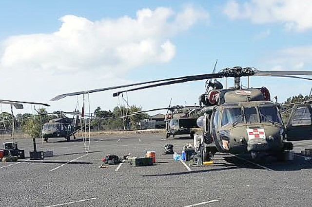 Shown are aircraft that were off-loaded from the Ocean Jazz vessel at the port of Gladstone, Australia. The aircraft rotors were re-attached there and flown to Townsville, located near the coast in northeast Australia. A total of 20 aircraft were sent to Australia used for air assaults, troop transportation, and air medical evacuation if required. (Photo by Maj. Phil Castillo, 402nd Army Field Support Brigade)