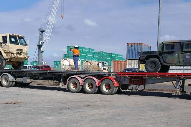 Shown are vehicles being loaded up on semi-trailers to be line-hauled to various locations near the coastline of northeast Australia.  (Photo by Maj. Phil Castillo, 402nd Army Field Support Brigade)