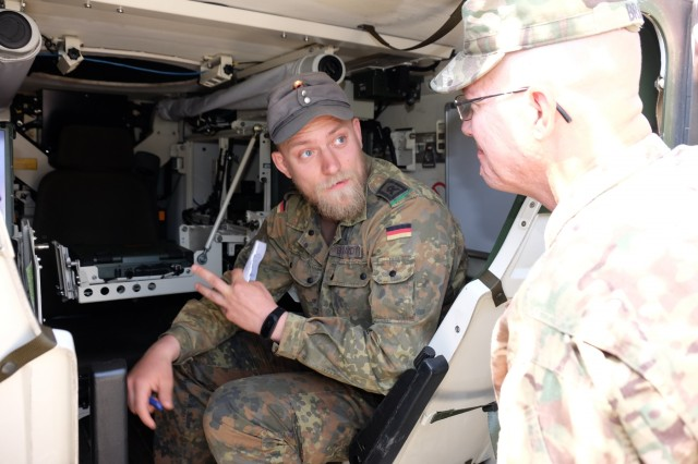 German Army Sgt. 1st Class Joel Burghardt (left) a fire mission team chief with the German Army 5th Company, 233rd Mountain Infantry Battalion, 23rd Mountain Infantry Brigade (5.Kompanie, 233. Gebirgsjaegerbatallion, 23. Gebirgsjaegerbrigade, Heer) demonstrates his unit�s Hagglunds BV206 amphibious tracked communications vehicle to Sgt. 1st Class Jason D. Brant, a logistics sergeant with the 209th Digital Liaison Detachment, 7th Mission Support Command during the Joint Warfighting Assessment 18 May 5, 2018 at USAG Bavaria, Grafenwoehr Training Area.