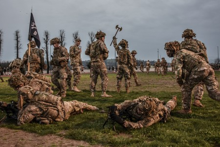 A battle ax is hoisted in the air to mark the finish line for paratroopers as they complete a 2.2 mile full combat load run for morning physical training as team members scramble to put their weapons systems into operation as they prepare for battle.