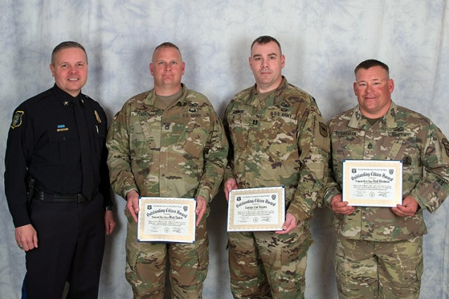 U.S. Army Sgt. 1st Class Neal Stratman, 2nd Battalion, 196th Regional Training Institute, South Dakota Army National Guard, right, Capt. Carl Stearns, 152nd Combat Sustainment Support Battalion, South Dakota Army National Guard, middle right, and Sgt. 1st Class Matt Tjaden, 1742nd Transportation Company, South Dakota Army National Guard, receive the Outstanding Citizen Award from Police Chief Matt Burns, Sioux Falls Police Department, in Sioux Falls, S.D., April 26, 2018. The award was presented for their actions and initiative at the scene of a car collision in Sioux Falls, S.D., March 7, 2018.