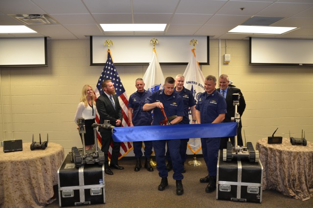 Two of the Coast Guard's new robots hold a ribbon in place while Commander Christopher Martin of the USCG's Office of Specialized Capabilities, does the honors.   The ribbon cutting signified the delivery of the first robots to be employed in the USCG's National Strike Force.  Martin spearheaded this important acquisition for the Coast Guard.