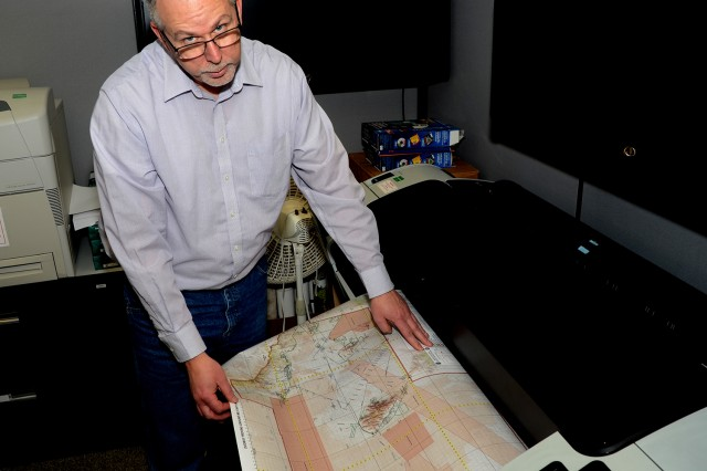 Jared Mathis, a GIS Analyst with the Environment Technology Office, stands in front of 44 inch map printer. Map making consists of a blend of science, technology, art and geographic elements to meet the requirements of specific chemical and biological defense testing at West Desert Test Center. Photo by Bonnie A. Robinson