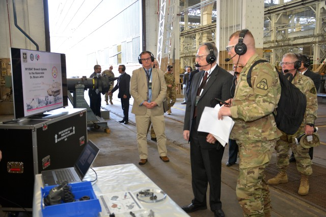 Lt. Col. Joseph Novak, right, briefing Assistant Secretary of the Army Bruce Jette, center, about the product improvements for the Paladin howitzer.  Novak is with the Program Executive Office for Ground Combat Systems.