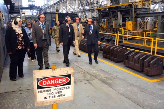 Arsenal Chief of Manufacturing John Zayhowski, right, briefing Assistant Secretary of the Army Bruce Jette, third from right, about manufacturing operations.